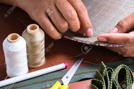 To sew- a needle pulling thread